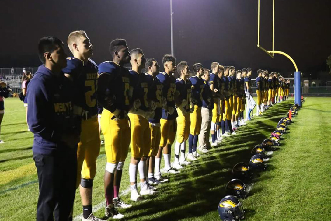 Varsity Football Locking Arms During National Anthem before Hinsdale South.