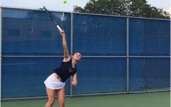 Julia Kostadinova, Senior, serving during her tennis match.
